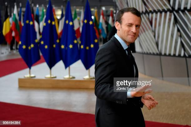 TOPSHOT France's President Emmanuel Macron gestures as he arrives on the first day of a summit of European Union leaders at the EU headquarters in...