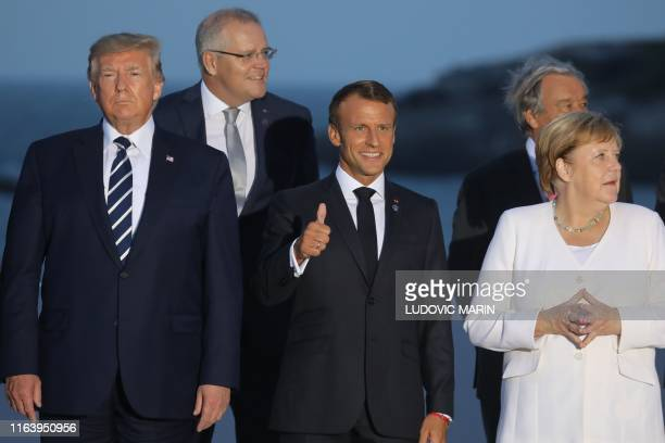France's President Emmanuel Macron gives a thumbs up, flanked by US President Donald Trump and Germany's Chancellor Angela Merkel during a family...