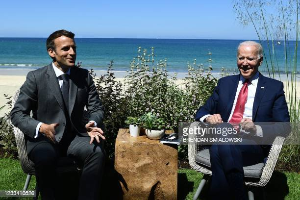 France's President Emmanuel Macron greets US President Joe Biden before a bilateral meeting during the G7 summit in Carbis bay, Cornwall on June 12,...