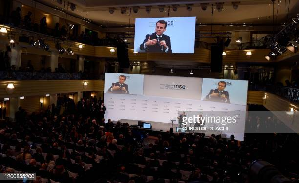 France's President Emmanuel Macron is displayed on screens as he talks with the chairman of the Munich Security Conference Wolfgang Ischinger during...