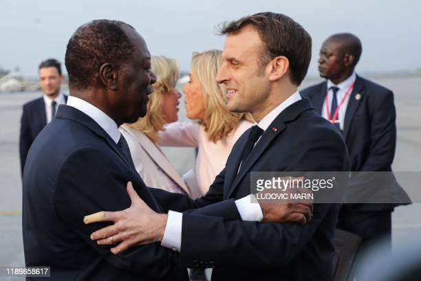 France's President Emmanuel Macron is greeted by Ivory Coast's President Alassane Ouattara, as his wife Dominique Folloroux-Ouattara greets Brigitte...
