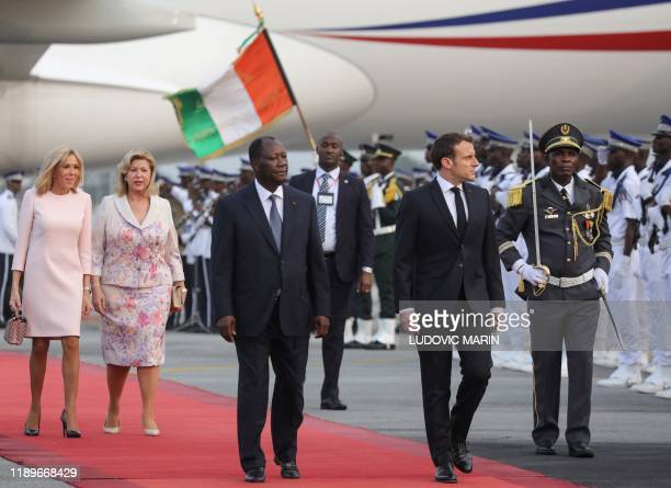 France's President Emmanuel Macron is greeted by Ivory Coast's President Alassane Ouattara next to their wives Brigitte Macron and Dominique...