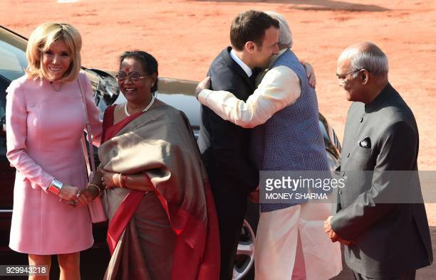 France's President Emmanuel Macron is hugged by India's Prime Minister Narendra Modi as Macron's wife Brigitte and India's President Ram Nath...