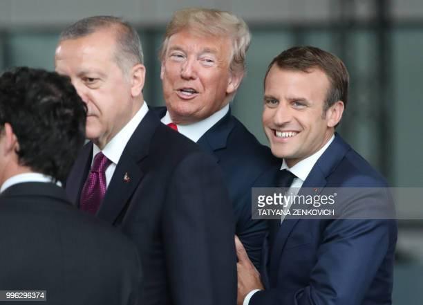 TOPSHOT France's President Emmanuel Macron jokes with US President Donald Trump next to Turkeys President Recep Tayyip Erdogan as they arrive for the...