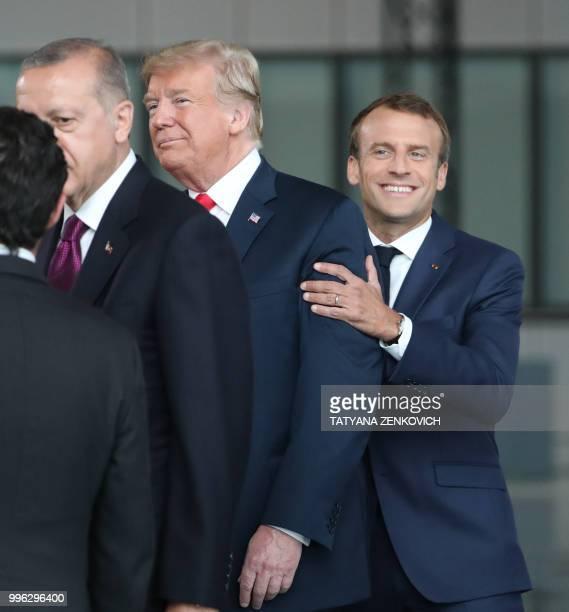 France's President Emmanuel Macron jokes with US President Donald Trump next to Turkeys President Recep Tayyip Erdogan as they arrive for the NATO...