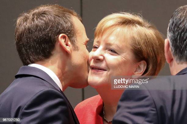France's President Emmanuel Macron kisses Germany's Chancellor Angela Merkel during the last day of the European Union leaders' summit, without...