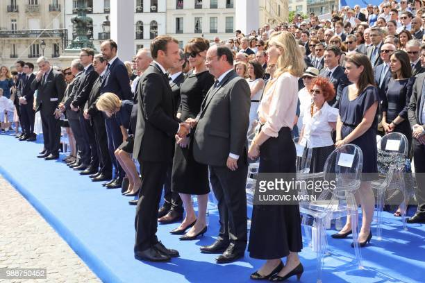 France's President Emmanuel Macron shakes hands with former French President Francois Hollande next to French actress Julie Gayet as they attend the...
