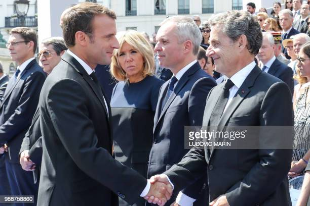France's President Emmanuel Macron shakes hands with former French President Nicolas Sarkozy nex to the President of the French National Assembly...