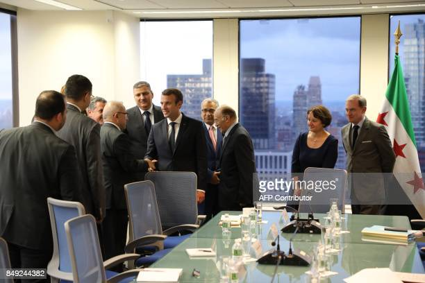 France's President Emmanuel Macron shakes hands with members of the Syrian delegation during his meeting with chief negotiator for the Syrian...