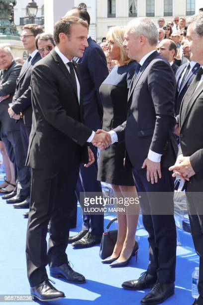 France's President Emmanuel Macron shakes hands with the President of the French National Assembly Francois de Rugy next the French President's wife...