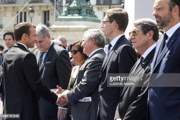 France's President Emmanuel Macron shakes hands with the son of late French politician and Holocaust survivor Simone Veil Jean Veil and his wife...