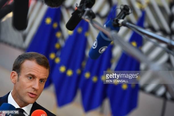 France's President Emmanuel Macron speaks to journalists as he arrives to take part in the last day of the European Union leaders' summit without...