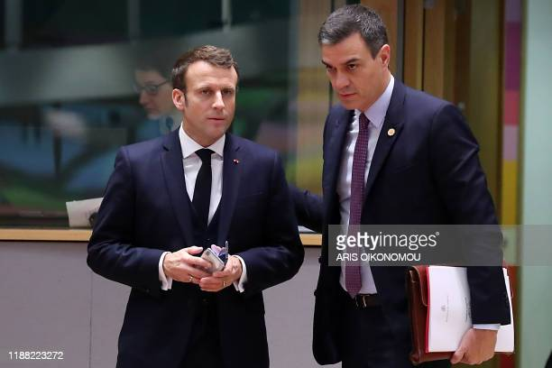 France's President Emmanuel Macron speaks with Spain's Prime Minister Pedro Sanchez as they arrive for the second day of a European Union Summit at...