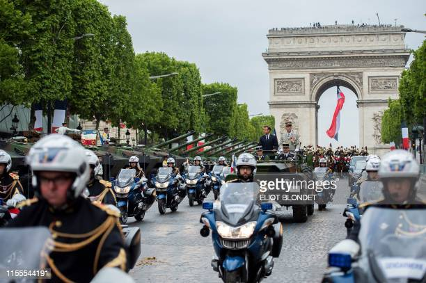 France's President Emmanuel Macron stands in an Acmat VLRA vehicle next to French Armies Chief Staff General Francois Lecointre as they review troops...