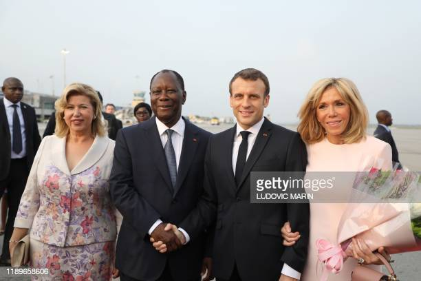 France's President Emmanuel Macron stands with his wife Brigitte Macron as he shakes the hand of Ivory Coast's President Alassane Ouattara...