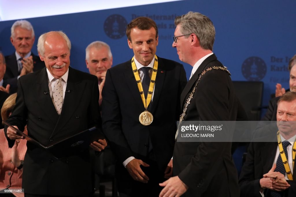 France's President Emmanuel Macron winks after receiving the Charlemagne prize award from Aachen Mayor Marcel Philipp (R) and chairman of the Prize board Juergen Linden (L) during the award ceremony on May 10, 2018 in Aachen, western Germany. - French President Emmanuel Macron received the prestigious Charlemagne Prize for his 'contagious enthusiasm' for strengthening EU cohesion and integration.