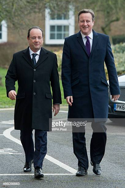 France's President Francois Hollande and British Prime Minister David Cameron arrive for the one day summit at RAF Brize Norton on January 31 2014...