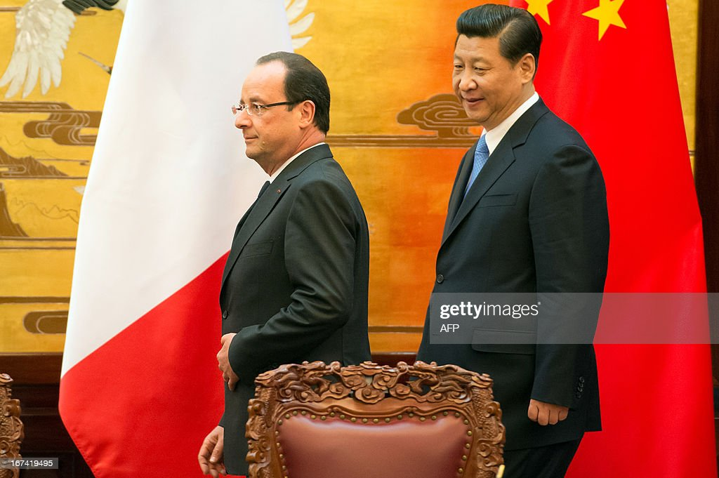France's President Francois Hollande (L) and his Chinese counterpart Xi Jinping (R) arrive to take part in a signing ceremony between France and China at the Great Hall of the People in Beijing on April 25, 2013. Hollande, accompanied by a high-powered business delegation, started a two-day visit to China, with trade rather than geopolitics at the top of the agenda.