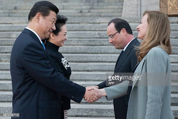 France's President Francois Hollande and his companion Valerie Trierweiler shake hands with Chinese President Xi Jinping and his wife Peng Liyuan as...