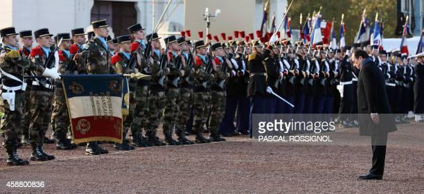 France's President Francois Hollande bows as he reviews troops during a ceremony to inaugurate the new war memorial at NotreDamedeLorette an...