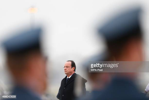France's President Francois Hollande listens to the French national anthem before reviewing the honour guard at RAF Brize Norton on January 31 2014...