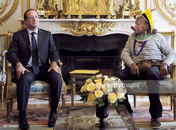 France's President Francois Hollande poses flanked by Amazonian Indian tribe Kayapo chief Raoni Metuktire prior to a meeting at the Elysee...