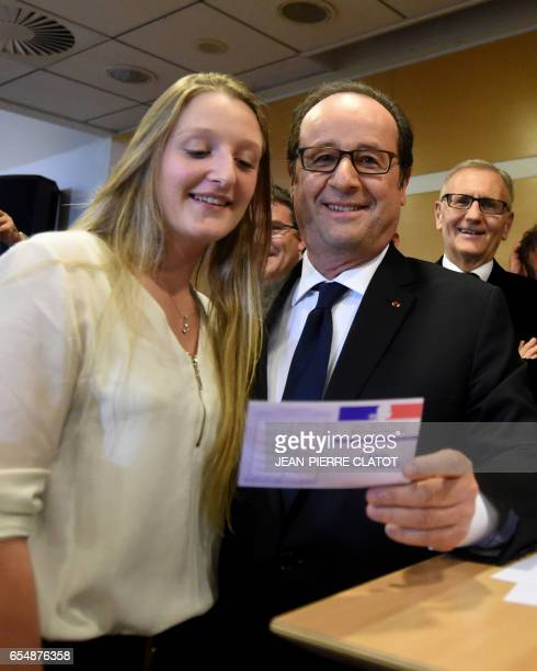 France's President Francois Hollande poses with a woman and her new voter registration card during a ceremony at the Crolles city hall on March 18...