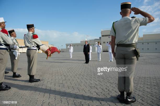 France's President Francois Hollande reviews the troops at the French naval base 'Camp de la Paix' in the Emirati capital Abu Dhabi on January 15...