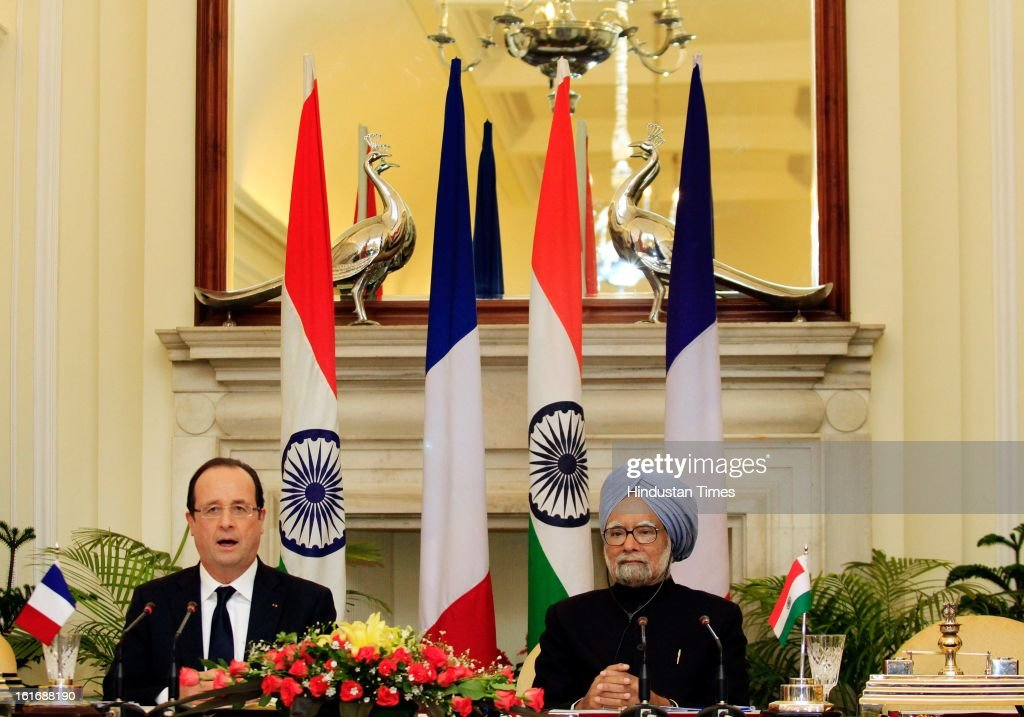 France's President Francois Hollande (L) speaks with the media as India's Prime Minister Manmohan Singh looks on after the signing of agreements ceremony on February 14, 2013 in New Delhi, India.