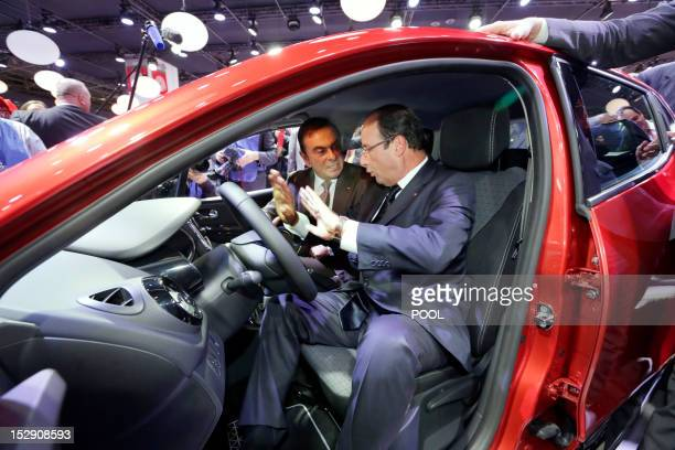 France's President Francois Hollande turns and speaks with Carlos Ghosn Chairman and CEO of the RenaultNissan Alliance as he sits in the new Renault...