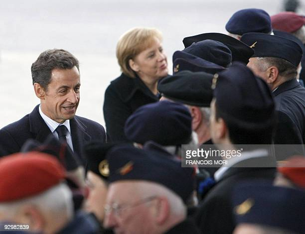 France's President Nicolas Sarkozy and German Chancellor Angela Merkel salute war veterans as they attend the Armistice Day ceremony marking 91 years...