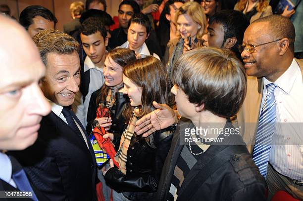 """France's President Nicolas Sarkozy is seen as he shakes hands during the inauguration of a platform """"Cine-High school"""" offering high schoolers..."""