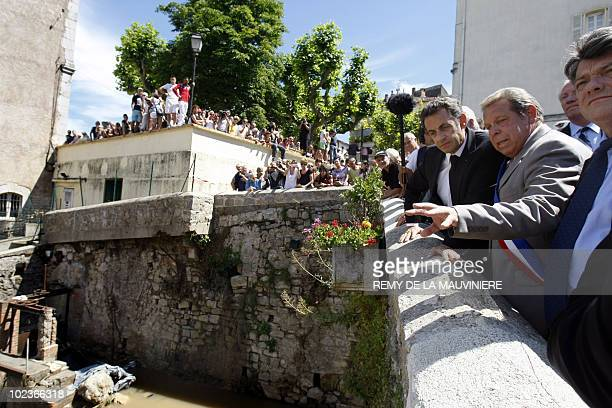 France's President Nicolas Sarkozy listens to explanations from TransenProvence's mayor Jacques Lecointe as he stands on a bridge over the Nartuby...