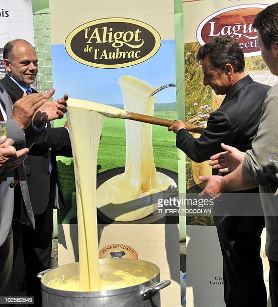 France's President Nicolas Sarkozy mixes Aligot a local speciality with cheese and potato puree in a farm in Brommat central France on July 1 2010...
