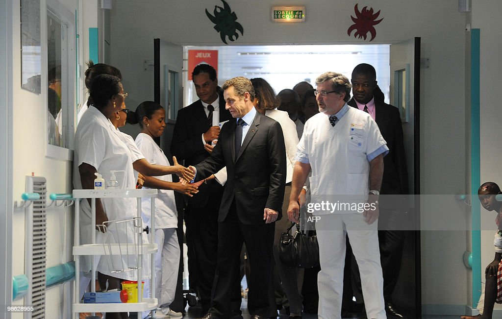 France's President Nicolas Sarkozy (C) salutes medical staff as he visits children wounded during Haiti's earthquake on February 17, 2010 in an hospital in Fort-de-France. Sarkozy travels to the French overseas departments of Martinique and French Guiana, few hours after he became first French president to visit Haiti, vowing to honor historic obligations to France's former slave colony and promising almost half a billion dollars in quake aid.