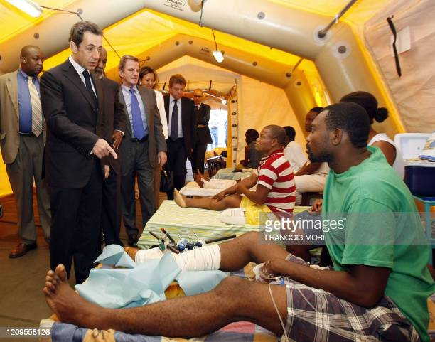 France's President Nicolas Sarkozy speaks with earthquake survivors during a visit at French field Hospital at Alexandre Dumas French school in...