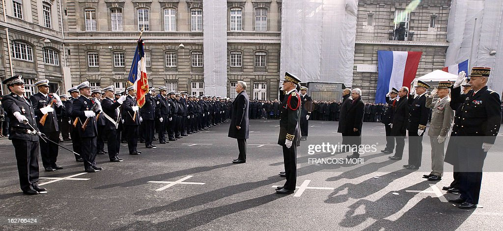 France's Prime Minister Jean-Marc Ayrault (C) pays homage in the yard of the Paris police prefecture on February 26, 2013 during a ceremony for the two slain policemen in Paris. An alleged drunk driver killed the two Paris police officers after slamming his black Land Rover into their cruiser during a high-speed chase on the ring road around Paris. At right, Jacques Mignaux, general director of the gendarmerie nationale