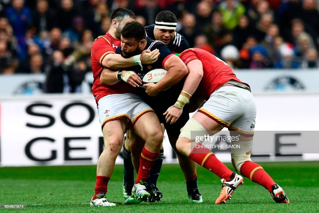 TOPSHOT - France's prop Rabah Slimani (C) is tackled during the Six Nations tournament Rugby Union match between France and Wales at the Stade de France in Saint-Denis, outside Paris, on March 18, 2017. /