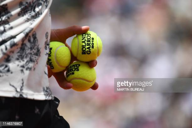 France's Quentin Halys holds the a 2019 French Open tennis tournament official balls as he plays against Japan's Kei Nishikori during their men's...