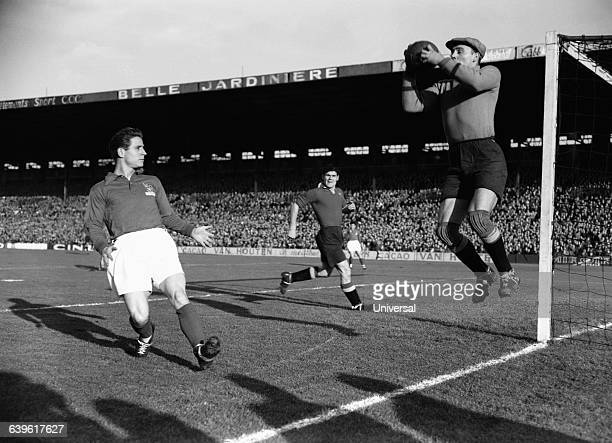 France's Raymond Kopa and Belgium's Armand Seghers during a friendly match between France and Belgium .