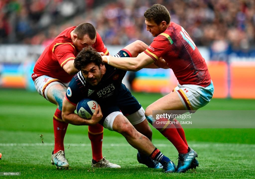 TOPSHOT - France's Remi Lamerat (C) is tackled by Wales' fly half Dan Biggar during the Six Nations tournament Rugby Union match between France and Wales at the Stade de France in Saint-Denis, outside Paris, on March 18, 2017. /