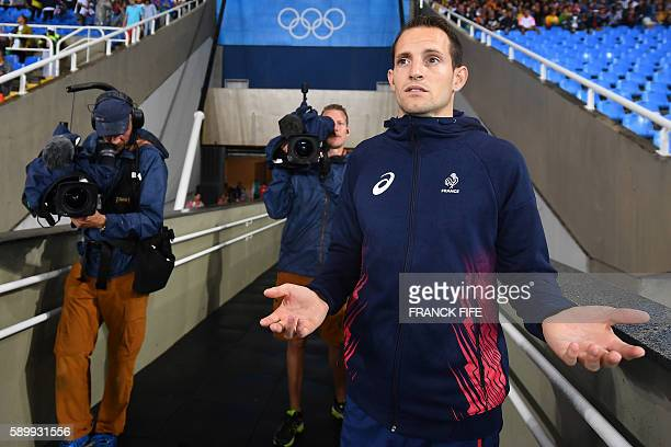 TOPSHOT France's Renaud Lavillenie gestures as the Men's Pole Vault Final is interrupted due to heavy rain during the athletics competition at the...