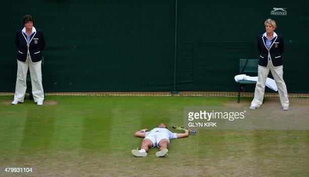 France's Richard Gasquet lays on the floor after beating Switzerland's Stan Wawrinka during their men's quarterfinals match on day nine of the 2015...