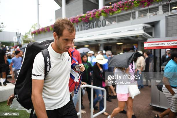 France's Richard Gasquet leaves the court after his game against Argentina's Leonardo Mayer was interrupted by the rain in their Qualifying Men's...