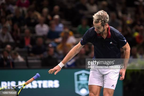 France's Richard Gasquet smashes his racquet on the court as he reacts during his men's singles second round tennis match against Jack Sock of the US...