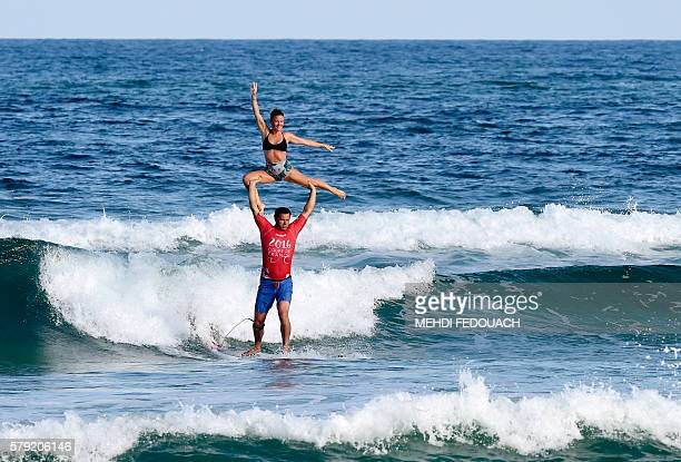 France's Rico Leroy and Sarah Burel compete in the International Tandem Surfing Championship on July 23 2016 in Biscarrosse / AFP / MEHDI FEDOUACH