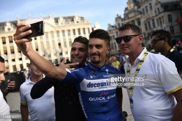 France's rider Julian Alaphilippe of Belgium's DeceuninckQuickStep takes a selfie with his coach and cousin Franck Alaphilippe and a fan during the...