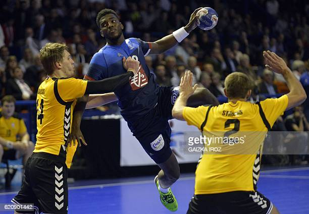 France's right back Dika Mem attempts a shot on goal and vies with Lithuania's Povilas Babarskas and Karolis Stropus during the 2018 EHF Men's...