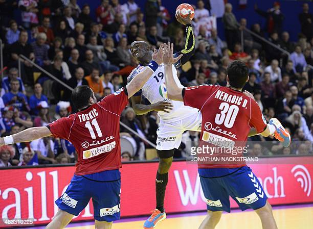 France's right wing Luc Abalo jumps to score on Serbia's pivot Alem Toskic and left back Drasko Nenadic during the men's EHF Euro 2014 Handball...