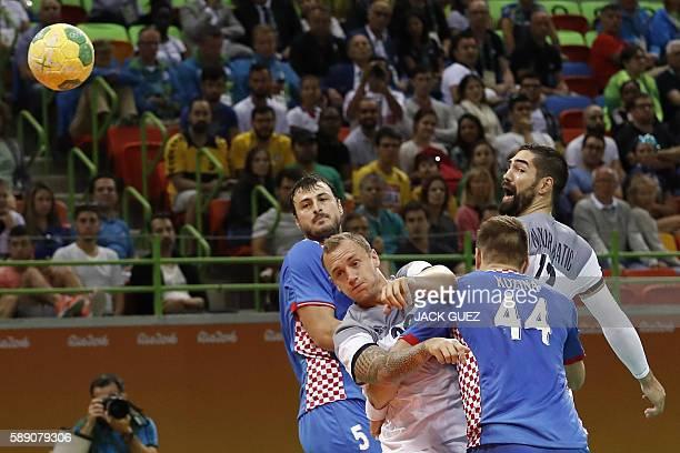 TOPSHOT France's right wing Valentin Porte shoots past Croatia's centre back Domagoj Duvnjak and France's centre back Nikola Karabatic during the...